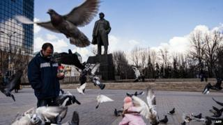 A man and a girl feed pigeons in front of a statue of late Soviet leader Vladimir Lenin on the central square in the city of Donetsk on 5 April 2015