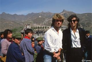 Young children sporting 'Mao' jackets and caps gape at George Michael (left) and Andrew Ridgeley, of the pop group Wham who are visiting the Great Wall as they promote the first-ever gig by a Western pop band in communist China, on 7 April 1985. (DO NOT REUSE IMAGE)