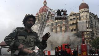 An Indian soldier prevents people from approaching the The Taj Mahal Hotel after a rescue operation in Mumbai on November 29, 2008