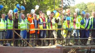 Volunteers and paid contractors celebrate the installation of new gates at Southland Lock, near Loxwood in West Sussex