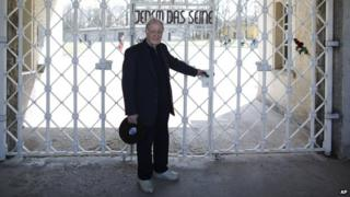 Henry Oster poses at the gate of the former Nazi concentration camp Buchenwald on 10 April 2015