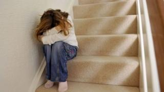 Library image of young girl sitting on a staircase, covering her face