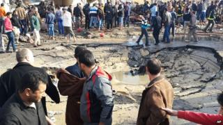 Egyptians gather around a crater left after a bombing in El-Arish on 11 April, 2015