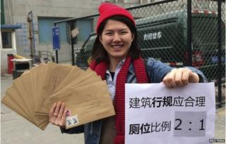 "Women activist Li Tingting, 25, poses with letters and a paper which read ""Construction regulations should be reasonable, bathroom proportion 2:1 (women/men)"" in this undated file handout picture taken in an unknown location in China, provided by a women""s rights group on 8 April 2015"
