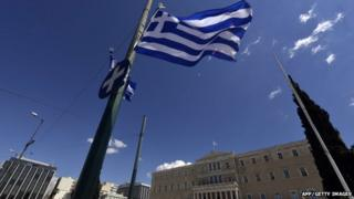 A greek flag flutters in front of the Greek parliament