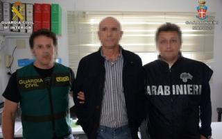 Lucio Morrone held by a Spanish civil guard and Italian police officer