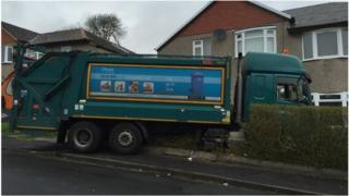 Bin lorry in front garden of house in Glasgow