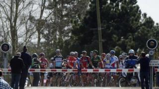 The pack is stopped at a level crossing during the 113th edition of the Paris-Roubaix one-day classic cycling race in Wallers on 12 April 2015.