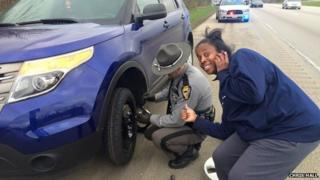 Picture of a white police officer changing a car tyre for an African American woman