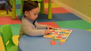 Carlson Chuen, aged two, plays with a puzzle during a session at the HKYTA, 25 February 2015