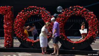 Visitors pay respects to Australia's Anzac soldiers as they pin a poppy to Wall of Remembrance in front of Queen Elizabeth cruise ship in Sydney on 3 March 2015