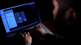 Man looks at image on laptop