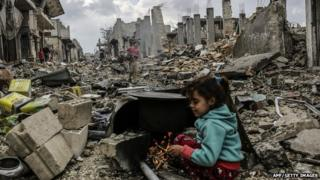 Syrian girls near destroyed buildings in the Syrian Kurdish town of Kobane