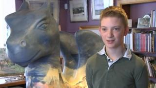 Kieron Williamson standing in front of his dragon