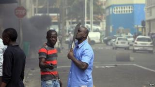 A foreigner holds a machete to protect himself after clashes broke out between a group of locals and police in Durban