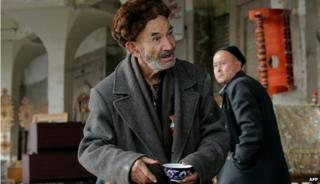 An older man holding a cup of tea in Tashkent