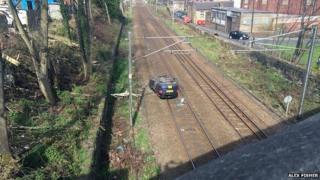 A car on the railway line at Shipley