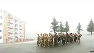 Officials in the Chinese county of Qianxi marching in a military-style remedial training camp.