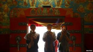Daughters of Ang Kaji Sherpa, one of the 16 Nepali Sherpa guides who were killed during an avalanche last year, light butter lamps in memory of their father at a monastery in Kathmandu April 18, 2015