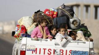 File photo: Children ride on the back of a pick-up truck with their luggage as they flee Saudi-led air strikes in Sanaa, 6 April 2015