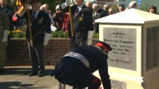 Man laying wreath at memorial