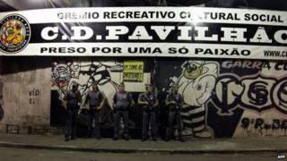 "Policemen stand guard outside the Corinthians fans ""Hall 9"" headquarters after the shooting"