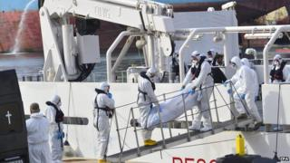 Members of the Italian coastguard ship Gregoretti disembark one of the 24 bodies of some of the 700 victims of the migrant boat disaster in Valletta, Malta