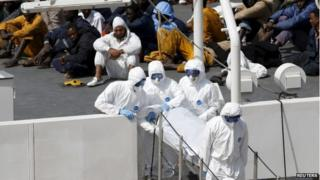 Armed Forces of Malta personnel in protective clothing carry the body of a dead immigrant off Italian coastguard ship Bruno Gregoretti as surviving migrants watch