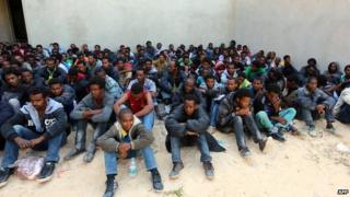 Some of the 340 illegal migrants who were rescued by the Libyan navy off the coast of the western town of Sabratha when their boat began to take on water, sit at a shelter on 12 May 2014