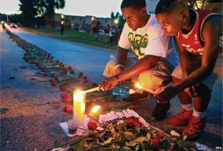 One of winning photographs taken by the staff of the St Louis Post-Dispatch shows a man and his brother lighting candles as roses stretch down the street near the spot where Michael Brown was shot in Ferguson