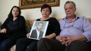 Sevag Balikci's family hold a photo of him