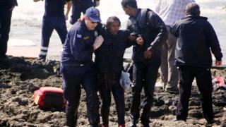 Greek coast guards help a migrant woman rescued after a boat carrying migrants sank off the island of Rhodes, south-eastern Greece, on 20 April