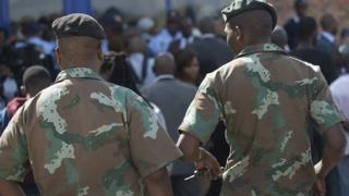 Two members of the South African Defence Force walk towards the Alexandra Police Station during a press conference by South Africa's Defence Minister, on 21 April 2015 in Alexandra Township, Johannesburg