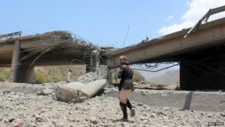 A man walks past a bridge targeted by Saudi-led coalition aircraft in Ibb, Yemen (21 April 2015)