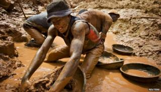A gold miner scoops mud while digging an open pit at the Chudja mine in the Kilomoto concession near the village of Kobu in this February 23, 2009