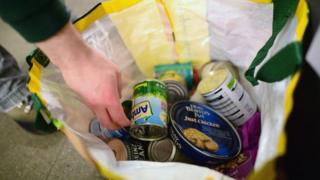 A volunteer packs food at a food bank