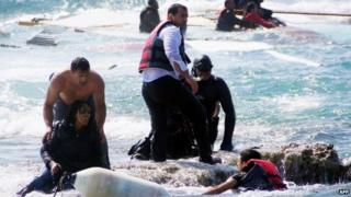 Local residents and rescue workers help a migrant woman after a boat carrying migrants sank off the island of Rhodes, south-eastern Greece
