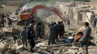 Afghan security forces inspect the site of a bomb blast in Kandahar