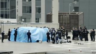 Police surrounding the drone which is covered in blue plastic