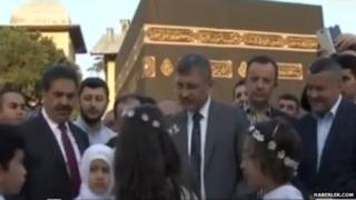 Hilmi Turkmen surrounded by people in front of the replica Kaaba