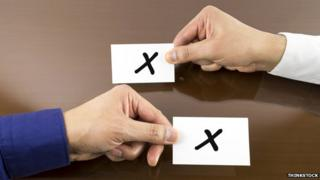 "Two hands swapping papers marked ""X"""