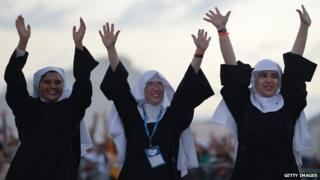Three nuns waving their arms in the air