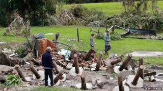 Men look at debris from homes destroyed after cyclonic winds on April 22, 2015 in Dungog, Australia.