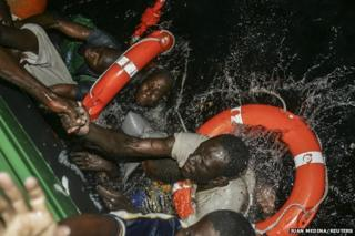 African migrants - including Isa and Ibrahim from Mali - try to climb aboard a Spanish Civil Guard vessel after their boat capsized
