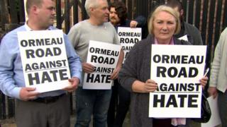 Residents held protest signs at the anti-hate crime demonstration