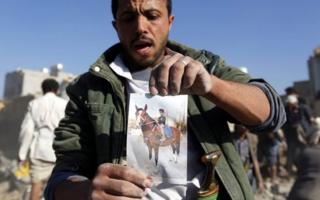 A Yemeni man holds a picture depicting a child riding a horse and claiming the child was killed in a Saudi air strike, in Sanaa, Yemen, 26 March 2015