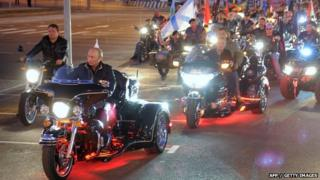"Russian Prime Minister Vladimir Putin (L) rides a motorbike as he takes part in the 16th annual motorbike festival held by ""The Night Wolves"" youth organisation in the southern Russian town of Novorossiysk, 29 August 2011"