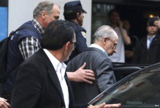 Rodrigo Rato (R) being escorted into a car by Spanish authorities