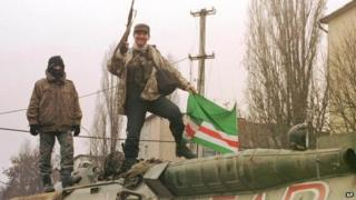 Chechen militants pose for press, as they stay atop APC, with graffiti in graffiti Cyrillic Akbar in Grozny Friday, Dec. 17, 1999.