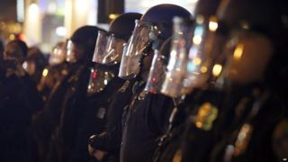 Police standing in a line with masks